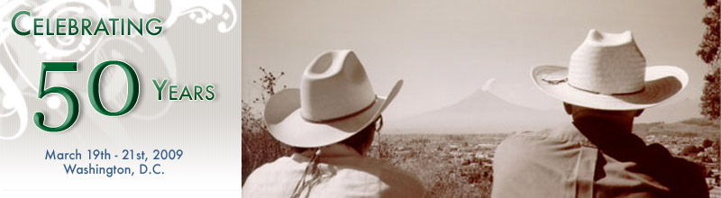 Celebrating 50 years, 3/19-3/21, 2009. Two men in cowboy hats watching a distant volcano